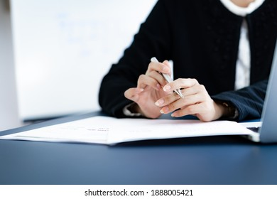 Asian business woman reviewing data in financial charts and graphs. Accounting concept