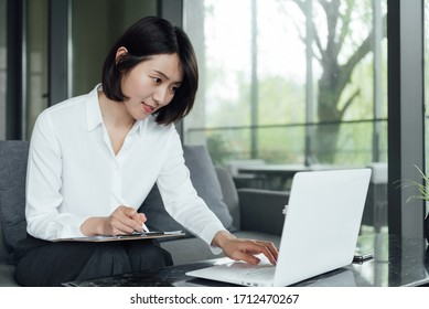 An Asian business woman with short hair is working