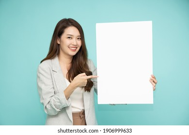 Asian business woman showing and holding blank white billboard isolated on green background