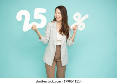 Asian business woman showing and holding 25% number or twenty five percent isolated over light green background