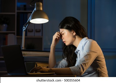 asian business woman sitting at desk headache overtime working late night. indoors office background