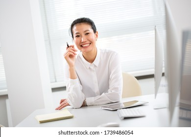 Asian business woman smiling at camera at workplace in an office