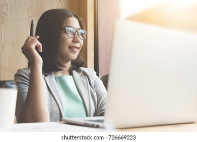 Asian Business woman smiling and  thinking about her work with laptop at her workplace.