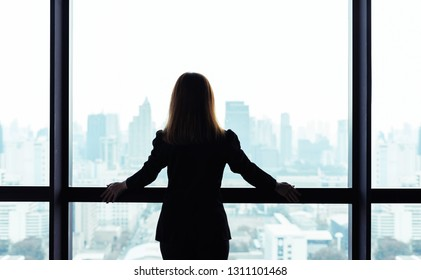 Asian business woman standing and looking out the window at city view background