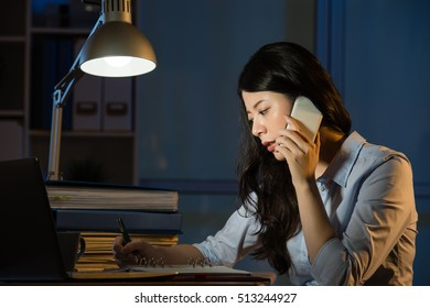 asian business woman talk on smartphone working overtime late night. indoors office background
