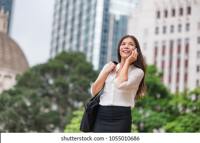 Asian business woman talking on phone walking commute to work office in Hong Kong city. Young businesswoman on smartphone happy. Multiracial Chinese Asian Caucasian female professional outside.