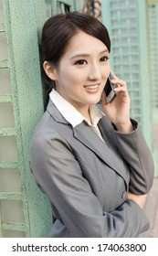 Asian business woman talking on smart phone in modern city.