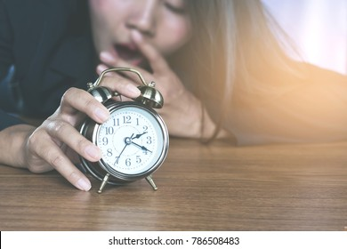Asian business woman tired from work  waking up by alarm clock and yawning still  sleepy ,office lifestyle concept background