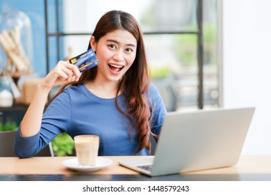 Asian business woman using credit card shopping online  working in coffee shop cafe with laptop smile and happy face concept success work