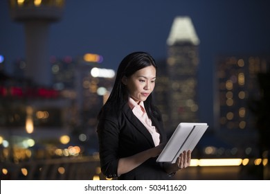 Asian business woman using a digital tablet PC in city at night.