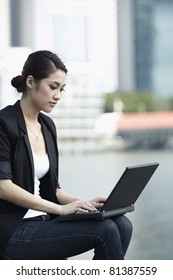 Asian Business woman using a Laptop outside