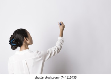 Asian business woman in white shirt writing on imaginary screen/whiteboard with blue marker on white background. Back view. Half length portrait. Teacher.