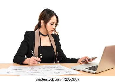 Asian business woman woker write idea project in paper with pen among chart, laptop, smartphone, graph document in office.