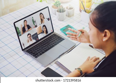 Asian business woman work from home with laptop and computer on table with meeting online and video conferencing.Concept of social distancing to stop the spread disease of Corona virus.