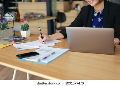 Asian business woman working in in coffee shop cafe with laptop paper work  (Business woman concept.)