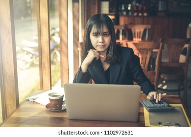 Asian business woman working in in coffee shop cafe with laptop paper work hand Holding coffee   (Business woman concept.)