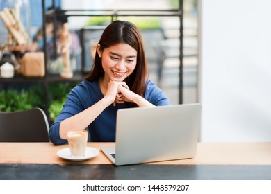 Asian business woman working in coffee shop cafe with laptop smile and happy face concept success work