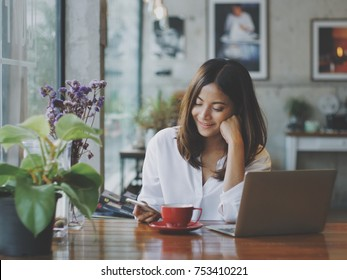 Asian business woman working in in coffee shop cafe with laptop