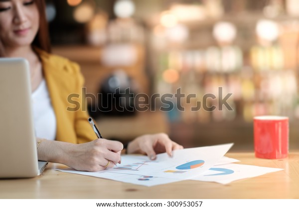 Asian business woman working with document and laptop in office.