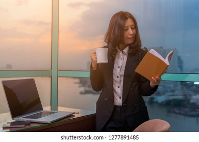 Asian Business woman working in office with documents and enjoy with coffee.