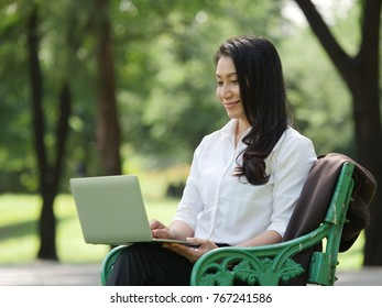 Asian business woman working in park with laptop