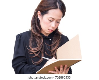 Asian business woman writing on brown book over white isolate background. Feeling attend, positive and confident. In black shirt and long hair. Make up in natural style.
