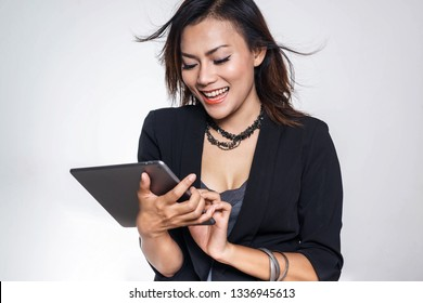 Asian business women are embracing her tablet and are happyFocus on face