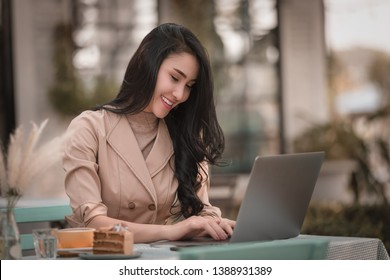 asian business women happy smiling sitting working creative freelance design on laptop via wifi internet in the park  autumn season in Thailand