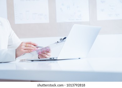 Asian business women reviewing data in financial charts and graphs