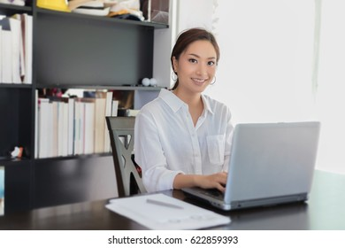Asian business women using notebook and  smiling happy for working at home office