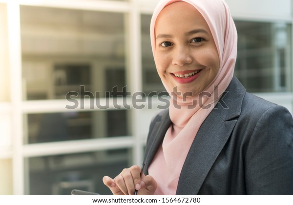 Asian Business Women wearing hijab smiling while using mobile phone