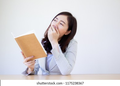 Asian business women in white suit holding and looking at a notebook while she yawning on white background.