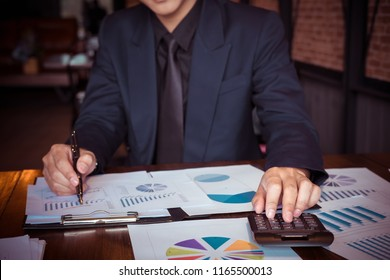 asian businessman or accountant working pointing graph discussion and analysis data charts and graphs and using a calculator to calculate  numbers.Business finances and accounting concept