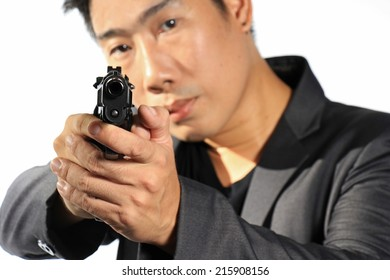 Asian Businessman aiming with handgun, Man in a suit preparing to shoot. Isolated on white. Semi-automatic handgun, 45 pistol.