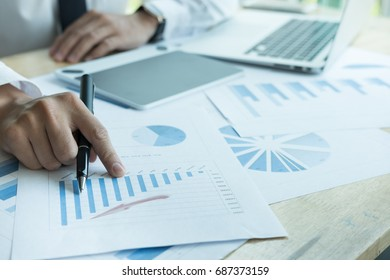 asian businessman analyze market chart at workplace.  young male entrepreneur man working with business document at office. analytic financial accounting graph plan report.  paperwork on table.