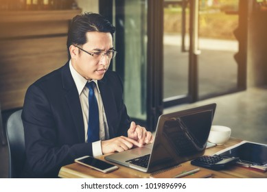 An Asian businessman is anxious about business with the information on his laptop.