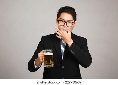 Asian businessman with beer whistle with fingers on gray background
