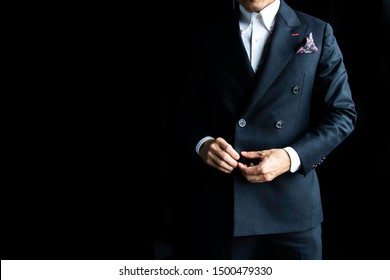 Asian businessman in a black suit is standing on a black background and has space for text.