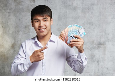 Asian businessman with bunch of Kazakh tenge in hand. Successful entrepreneur has earned a lot of money on transactions and sale of stock.