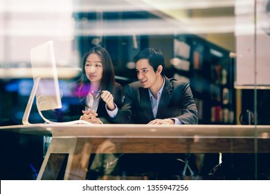 Asian businessman and businesswoman discussing work in the office