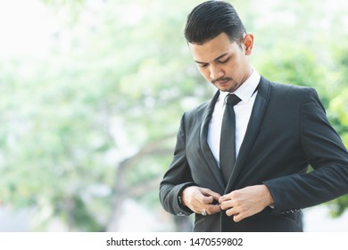Asian businessman button his suit, get ready for work.