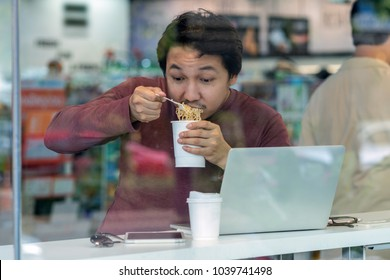 Asian businessman in casual suit eating noodles with urgent action in rush hour at the desk beside the glass in modern office, Business work hard concept