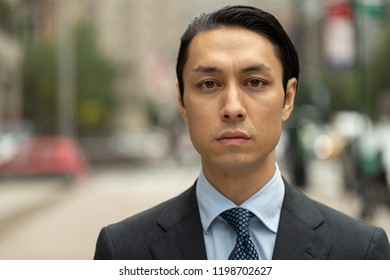 Asian businessman in city serious face portrait