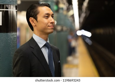 Asian businessman in city standing on a subway platform smile happy