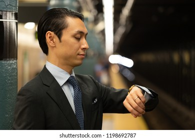 Asian businessman in city standing at platform