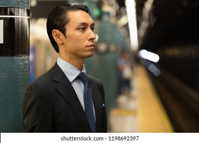 Asian businessman in city standing at subway platform thinking
