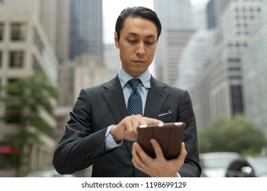 Asian businessman in city walking street using tablet computer