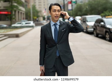 Asian businessman in city walking talking on cell phone