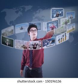 Asian businessman clicking on futuristic screen over blue digital world map
