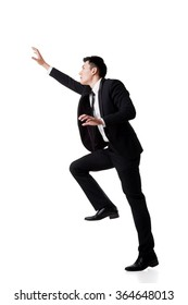 Asian businessman climbing, full length portrait isolated